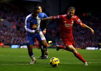 LIVERPOOL, ENGLAND - FEBRUARY 12:  Charles N' Zogbia of Wigan Athletic competes with Milan Jovanovic of Liverpool during the Barclays Premier League match between Liverpool and Wigan Athletic at Anfield on February 12, 2011 in Liverpool, England.  (Photo