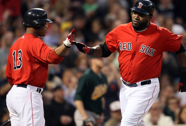 BOSTON, MA - JUNE 03:  David Ortiz #34 of the Boston Red Sox celebrates his run with teammate Carl Crawford #13 after Ortiz scored in the third inning against the Oakland Athletics on June 3, 2011 at Fenway Park in Boston, Massachusetts.  (Photo by Elsa/G