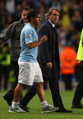 MANCHESTER, ENGLAND - MAY 17:  Carlos Tevez of Manchester City walks on to the pitch for a lap of honour with his manager Roberto Mancini after the Barclays Premier League match between Manchester City and Stoke City at City of Manchester Stadium on May 1