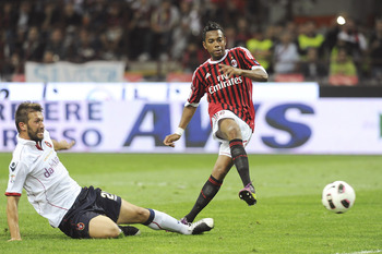 MILAN, ITALY - MAY 14:  Robinho (R) of Milan shoots at goal as he is challenged by Gabriele Perico of Cagliari during the Serie A match between AC Milan and Cagliari Calcio at Stadio Giuseppe Meazza on May 14, 2011 in Milan, Italy.  (Photo by Dino Panato/