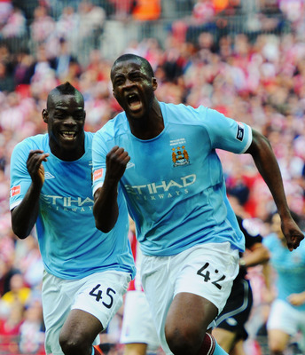 LONDON, ENGLAND - MAY 14:  Yaya Toure (R) of Manchester City celebrates with Mario Balotelli (L) after scoring during the FA Cup sponsored by E.ON Final match between Manchester City and Stoke City at Wembley Stadium on May 14, 2011 in London, England.  (