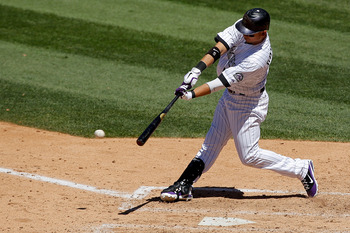 DENVER, CO - JUNE 15: Carlos Gonzalez #5 of the Colorado Rockies singles to center field scoring catcher Jose Morales #26 of the Colorado Rockies in the fifth inning at Coors Field on June 15, 2011 in Denver, Colorado. The Rockies defeated the Padres 6-3.