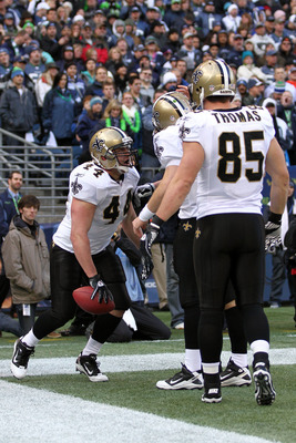 SEATTLE, WA - JANUARY 08:  Heath Evans #44 of the New Orleans Saints celebrates his one-yard touchdown reception with teammates Drew Brees #9 and David Thomas #85 in the first quarter against the Seattle Seahawks during the 2011 NFC wild-card playoff game