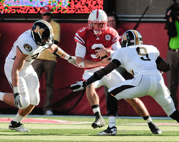 LINCOLN, NE - OCTOBER 30: Quarterback Taylor Martinez #3 of the Nebraska Cornhuskers tries to slip between Missouri Tiger defenders during first half action of their game at Memorial Stadium on October 30, 2010 in Lincoln, Nebraska. Nebraska Defeated Miss