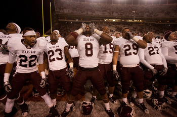 AUSTIN, TX - NOVEMBER 25:  Texas A&M players (L-R) Dustin Harris #22, Ben Malena #23, Jeff Fuller #8, Michael Lamothe #19, Blane Cheatham #29, and C.J. Jones #27 celebrate Texas A&M's 24-17 win over the University of Texas at Darrell K. Royal-Texas Memori