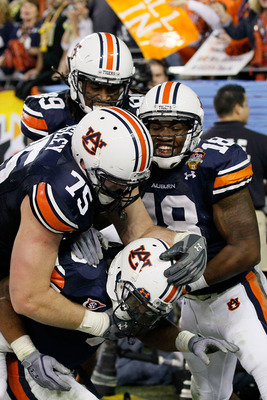 GLENDALE, AZ - JANUARY 10:  Michael Dyer #5 of the Auburn Tigers celebrates with teammates Brandon Mosley #75 and Kodi Burns #18 after he ran the ball for 16-yards and is called down at the one-yardline with 10 seconds remaining in the fourth quarter agai