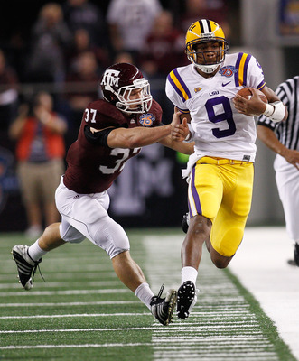 ARLINGTON, TX - JANUARY 07:  Jordan Jefferson #9 of the Louisiana State University Tigers is pushed out of bounds by Michael Hodges #37 of the Texas A&M Aggies during the AT&T Cotton Bowl at Cowboys Stadium on January 7, 2011 in Arlington, Texas.  (Photo
