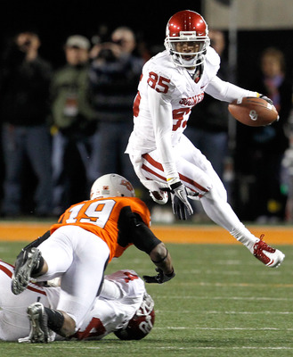 STILLWATER, OK - NOVEMBER 27:  Wide receiver Ryan Broyles #85 of the Oklahoma Sooners leaps over cornerback Brodrick Brown #19 of the Oklahoma State Cowboys at Boone Pickens Stadium on November 27, 2010 in Stillwater, Oklahoma.  The Sooners beat the Cowbo