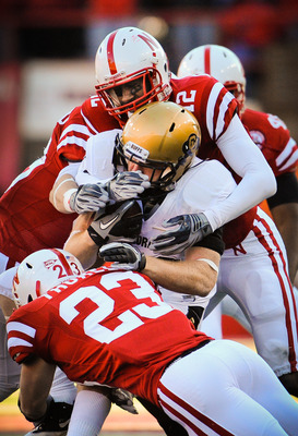 LINCOLN, NE - NOVEMBER 26: Courtney Osborne #12 and Lance Thorell #23 of the Nebraska Cornhuskers wrap up Parke Robbins #22 of the Colorado Buffaloes during their game at Memorial Stadium on November 26, 2010 in Lincoln, Nebraska. Nebraska defeated Colora