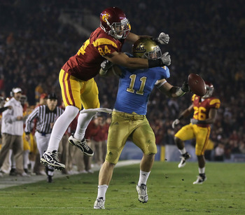 PASADENA, CA - DECEMBER 04:  Sean Westgate #11 of the UCLA Bruins breaks up a pass intended for Jordan Cameron #84 of the USC Trojans during the first half at the Rose Bowl on December 4, 2010 in Pasadena, California. USC defeated UCLA 28-14.  (Photo by J