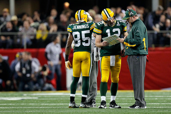 ARLINGTON, TX - FEBRUARY 06:  Aaron Rodgers #12 and head coach Mike McCarthy of the Green Bay Packers talk during a stop in play against the Pittsburgh Steelers during Super Bowl XLV at Cowboys Stadium on February 6, 2011 in Arlington, Texas.  (Photo by K