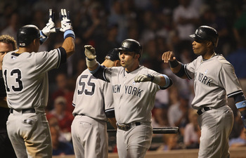 CHICAGO, IL - JUNE 19:  Nick Swisher #33 of the New York Yankees celebrates his three-run home run in the 8th inning with teammates Alex Rodriguez #13 and Robinson Cano #24 against the Chicago Cubs at Wrigley Field on June 19, 2011 in Chicago, Illinois.