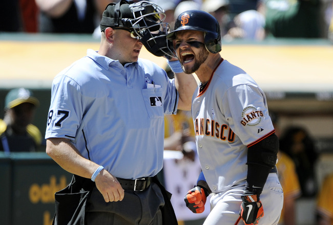 OAKLAND, CA -  JUNE 19: Cody Ross #13 of the San Francisco Giants is upset with a called third strike by home-plate umpire Scott Barry #87 that ended a MLB baseball game against the Oakland Athletics, June 19, 2011 at the Oakland-Alameda County Coliseum i