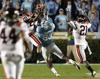 CHAPEL HILL, NC - NOVEMBER 13:  Jayron Hosley #20 of the Virginia Tech Hokies makes an interception as teammate Rashad Carmichael #21 watches on with Dwight Jones #83 of the North Carolina Tar Heels during their game at Kenan Stadium on November 13, 2010