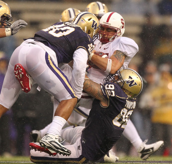 SEATTLE - OCTOBER 30:  Running back Tyler Gaffney #25 of the Stanford Cardinal is tackled by Everrette Thompson #92 and Mason Foster #40 of  the Washington Huskies on October 30, 2010 at Husky Stadium in Seattle, Washington. Stanford defeated Washington 4