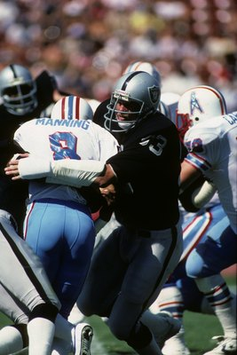 LOS ANGELES - SEPTEMBER 11:  Linebacker Ted Hendricks #83 of the Los Angeles Raiders tackles Houston Oilers quarterback Archie Manning #8 during the game at the Los Angeles Memorial Coliseum on September 11, 1983 in Los Angeles, California.  The Raiders w