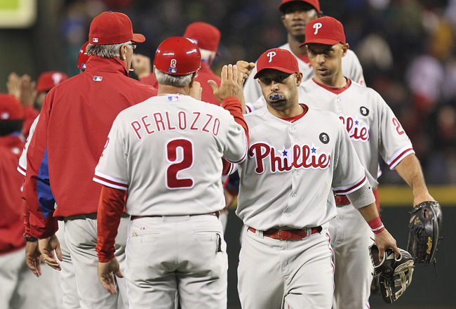 SEATTLE - JUNE 18:  Shane Victorino #8 of the Philadelphia Phillies is congratulated by first base coach Sam Perlozzo #2 after defeating the Seattle Mariners 5-1 at Safeco Field on June 18, 2011 in Seattle, Washington. (Photo by Otto Greule Jr/Getty Image