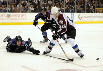 LOS ANGELES, CA - MARCH 22:  Paul Stasny #26 of the Colorado Avalanche has the puck knocked away by Matt Greene #2 of the Los Angeles Kings during the first period on March 22, 2010 at the the Staples Center in Los Angeles, California.  (Photo by Harry Ho