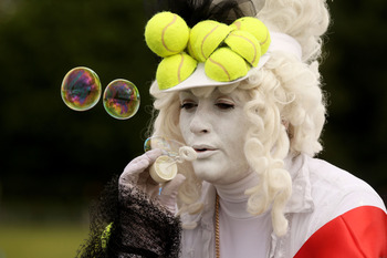 LONDON, ENGLAND - JUNE 21:  A tennis fan blows bubbles while waiting in a queue to enter the grounds on Day Two of the Wimbledon Lawn Tennis Championships at the All England Lawn Tennis and Croquet Club on June 21, 2011 in London, England.  (Photo by Oli