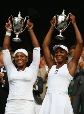 WIMBLEDON, ENGLAND - JULY 04:  Venus Williams of USA (L) and Serena Williams of USA celebrate victory with their trophies after the women's doubles final match against Samantha Stosur of Australia and Rennae Stubbs of Australia on Day Twelve of the Wimble