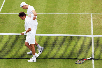 LONDON, ENGLAND - JUNE 24:  John Isner of USA (top) celebrates winning on the third day of his first round match against Nicolas Mahut of France on Day Four of the Wimbledon Lawn Tennis Championships at the All England Lawn Tennis and Croquet Club on June