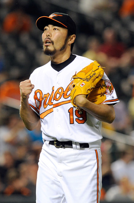 BALTIMORE, MD - JUNE 06:  Koji Uehara #19 of the Baltimore Orioles celebrates after the final out in the eighth inning against the Oakland Athletics at Oriole Park at Camden Yards on June 6, 2011 in Baltimore, Maryland. The Orioles won the game 4-2.  (Pho