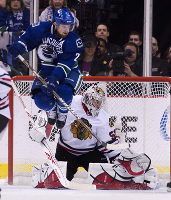 VANCOUVER, CANADA - APRIL 26: Daniel Sedin #22 of the Vancouver Canucks jumps out of the way as goalie Corey Crawford #50 of the Chicago Blackhawks makes a pad save during the second period in Game Seven of the Western Conference Quarterfinals during the