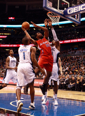 ORLANDO, FL - FEBRUARY 08:  Ike Diogu #50 of the Los Angeles Clippers attempts a shot against Dwight Howard #12 of the Orlando Magic during the game at Amway Arena on February 8, 2011 in Orlando, Florida.  NOTE TO USER: User expressly acknowledges and agr
