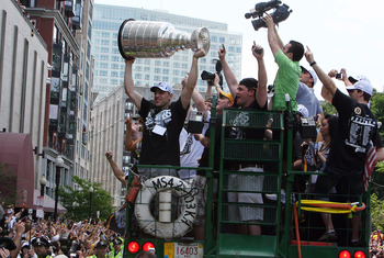 BOSTON, MA  - JUNE 18: Milan Lucic of the Boston Bruins holds the Stanley Cup up to the cheering fans during the Stanley Cup victory parade on June 18, 2011 in Boston, Massachusetts.  (Photo by Gail Oskin/Getty Images)