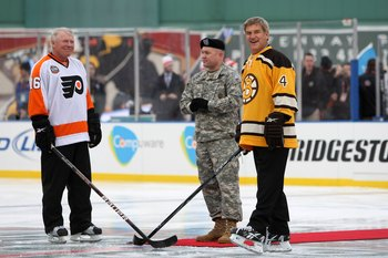 BOSTON - JANUARY 01:  Staff Sergeant Ryan R. LaFrance (C) prepares to drop the ceremonial first puck for Bobby Clarke #16 (L) honorary captain of the Philadelphia Flyers and Bobby Orr #4 (R) honorary captain of the Boston Bruins during the 2010 Bridgeston