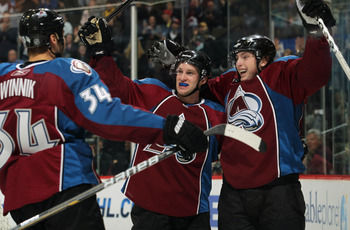 DENVER, CO - MARCH 22:  (R-L) Matt Duchene #9 of the Colorado Avalanche celebrates his third period goal with teammate Mark Oliver #40 and Daniel Winnik #34 to tie the score 3-3 in the third period against the Columbus Blue Jackets at the Pepsi Center on