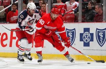 DETROIT - APRIL 16:  Michael Peca #19 of the Columbus Blue Jackets defends against Henrik Zetterberg #40 of the Detroit Red Wings during Game One of the Western Conference Quarterfinals of the 2009 Stanley Cup Playoffs on April 16, 2009 at Joe Louis Arena