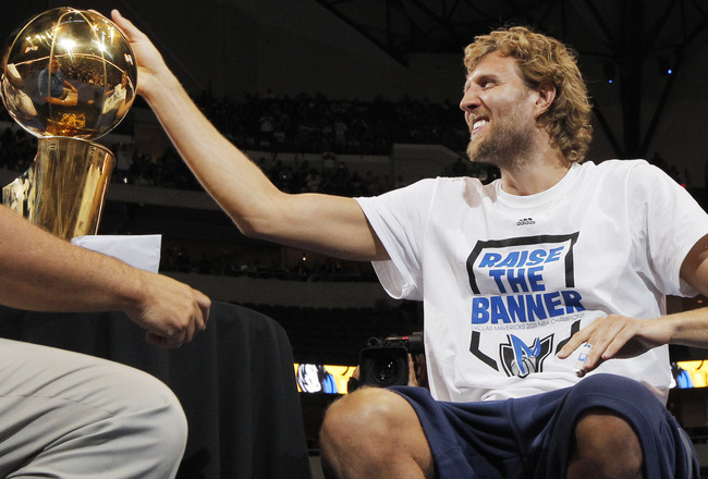 DALLAS, TX - JUNE 16: Forward Dirk Nowitzki of the Dallas Mavericks touches the Larry O'Brien trophy during the Dallas Mavericks Victory celebration on June 16, 2011 in Dallas, Texas. (Photo by Brandon Wade/Getty Images)
