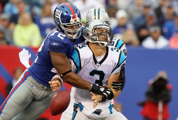 EAST RUTHERFORD, NJ - SEPTEMBER 12:  Osi Umenyiora #72 of the New York Giants forces a fumble against Matt Moore #3 of the Carolina Panthers during the fourth quarter on September 12, 2010 at the New Meadowlands Stadium in East Rutherford, New Jersey. The