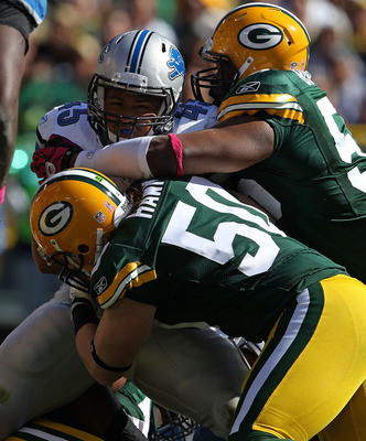 GREEN BAY, WI - OCTOBER 03: A.J. Hawk #50 and Desmond Bishop #55 of the Green Bay Packers tackle Jerome Felton #45 of the Detroit Lions at Lambeau Field on October 3, 2010 in Green Bay, Wisconsin. The Packers defeated the Lions 28-26. (Photo by Jonathan D