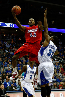 NEWARK, NJ - DECEMBER 22:  Chris Wright #33 of the Dayton Flyers drives for a shot attempt against Jeff Robinson #32 of the Seton Hall Pirates at Prudential Center on December 22, 2010 in Newark, New Jersey.  (Photo by Chris Chambers/Getty Images)