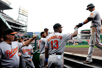 WASHINGTON, DC - JUNE 19: J.J. Hardy #2 of the Baltimore Orioles is greeted in the dugout after scoring against the Washington Nationals in the fifth inning at Nationals Park on June 19, 2011 in Washington, DC. The Baltimore Orioles won, 7-4. (Photo by Pa