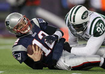 Shaun Ellis (right) sacking Tom Brady (left) in the Jets playoff victory against the Patriots in January 2011.