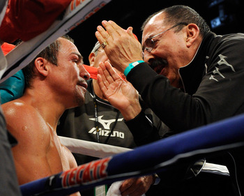 LAS VEGAS - JULY 31:  WBA/WBO lightweight champion Juan Manuel Marquez (L) gets advice from his trainer Ignacio 'Nacho' Beristain between rounds during his bout against Juan Diaz at the Mandalay Bay Events Center July 31, 2010 in Las Vegas, Nevada. Marque