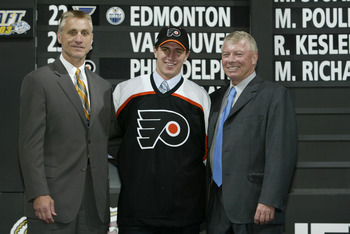 NASHVILLE, TN - JUNE 21:  (L to R) Paul Holmgren, first round draft pick (#24 overall) Mike Richards, Bob Clarke of the Philadelphia Flyers pose for a portrait on stage during the 2003 NHL Entry Draft at the Gaylord Entertainment Center on June 21, 2003 i