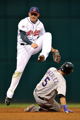 CLEVELAND, OH - JUNE 20:  Asdrubal Cabrera #13 of the Cleveland Indians leaps over Carlos Gonzalez #5 of the Colorado Rockies as he completes a double play in the third inning at Progressive Field on June 20, 2011 in Cleveland, Ohio.  (Photo by Jamie Saba