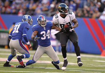 EAST RUTHERFORD, NJ - NOVEMBER 28:  Marcedes Lewis #89  of the Jacksonville Jaguars makes a catch as Deon Grant #34 and Aaron Ross #31 of the New York Giants defend during their game on November 28, 2010 at The New Meadowlands Stadium in East Rutherford,