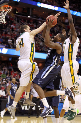 CLEVELAND, OH - MARCH 18: Corey Stokes #24 of the Villanova Wildcats drives to the basket against Luke Hancock #14 and Mike Morrison #22 of the George Mason Patriots during the second round of the 2011 NCAA men's basketball tournament at Quicken Loans Are