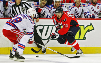 WASHINGTON , DC - APRIL 23:  Marcus Johansson #90 of the Washington Capitals skates the puck against Bryan McCabe #28 of the New York Rangers in Game Five of the Eastern Conference Quarterfinals during the 2011 NHL Stanley Cup Playoffs at the Verizon Cent