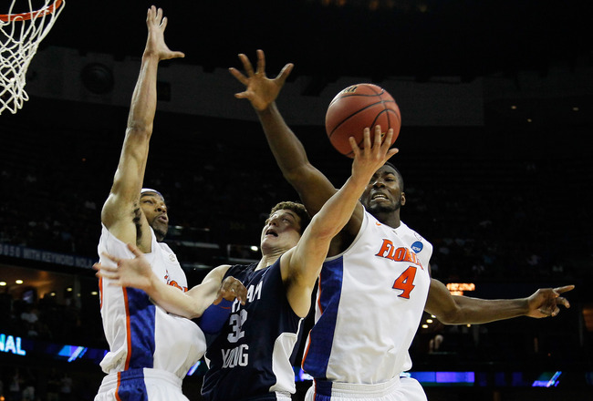 NEW ORLEANS, LA - MARCH 24:  Jimmer Fredette #32 of the Brigham Young Cougars goes up for a shot between Alex Tyus #23 and Patric Young #4 of the Florida Gators during the Southeast regional of the 2011 NCAA men's basketball tournament at New Orleans Aren