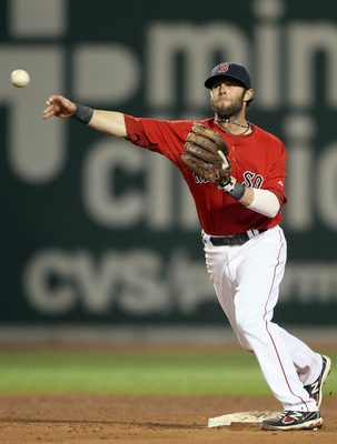 BOSTON, MA - JUNE 03:  Dustin Pedroia #15 of the Boston Red Sox turns the double play in the seventh inning against the Oakland Athletics on June 3, 2011 at Fenway Park in Boston, Massachusetts.  (Photo by Elsa/Getty Images)