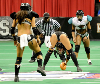 LAS VEGAS, NV - FEBRUARY 06:  Natalie Jahnke #16 of the Los Angeles Temptation prepares to hike the ball to quarterback Ashley Salerno #8 in front of Marirose Roach #6 of the Philadelphia Passion during the Lingerie Football League's Lingerie Bowl VIII at
