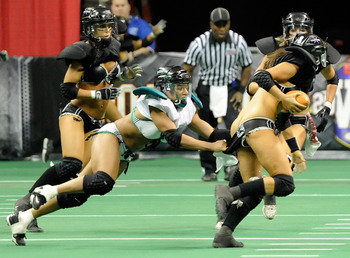 LAS VEGAS, NV - FEBRUARY 06:  (EDITORS NOTE: Image contains nudity.) Marirose Roach #6 of the Philadelphia Passion tries to tackle quarterback Ashley Salerno #8 of the Los Angeles Temptation during the Lingerie Football League's Lingerie Bowl VIII at the