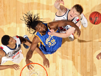 DENVER, CO - MARCH 19:  Kenneth Faried #35 of the Morehead State Eagles fights for a loose ball against Justin Harper #32 and Dan Geriot #41 of the Richmond Spiders during the third round of the 2011 NCAA men's basketball tournament at Pepsi Center on Mar