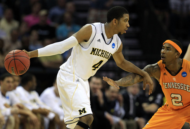 CHARLOTTE, NC - MARCH 18:  Darius Morris #4 of the Michigan Wolverines moves the ball against Melvin Goins #2 of the Tennessee Volunteers in the second half during the second round of the 2011 NCAA men's basketball tournament at Time Warner Cable Arena on